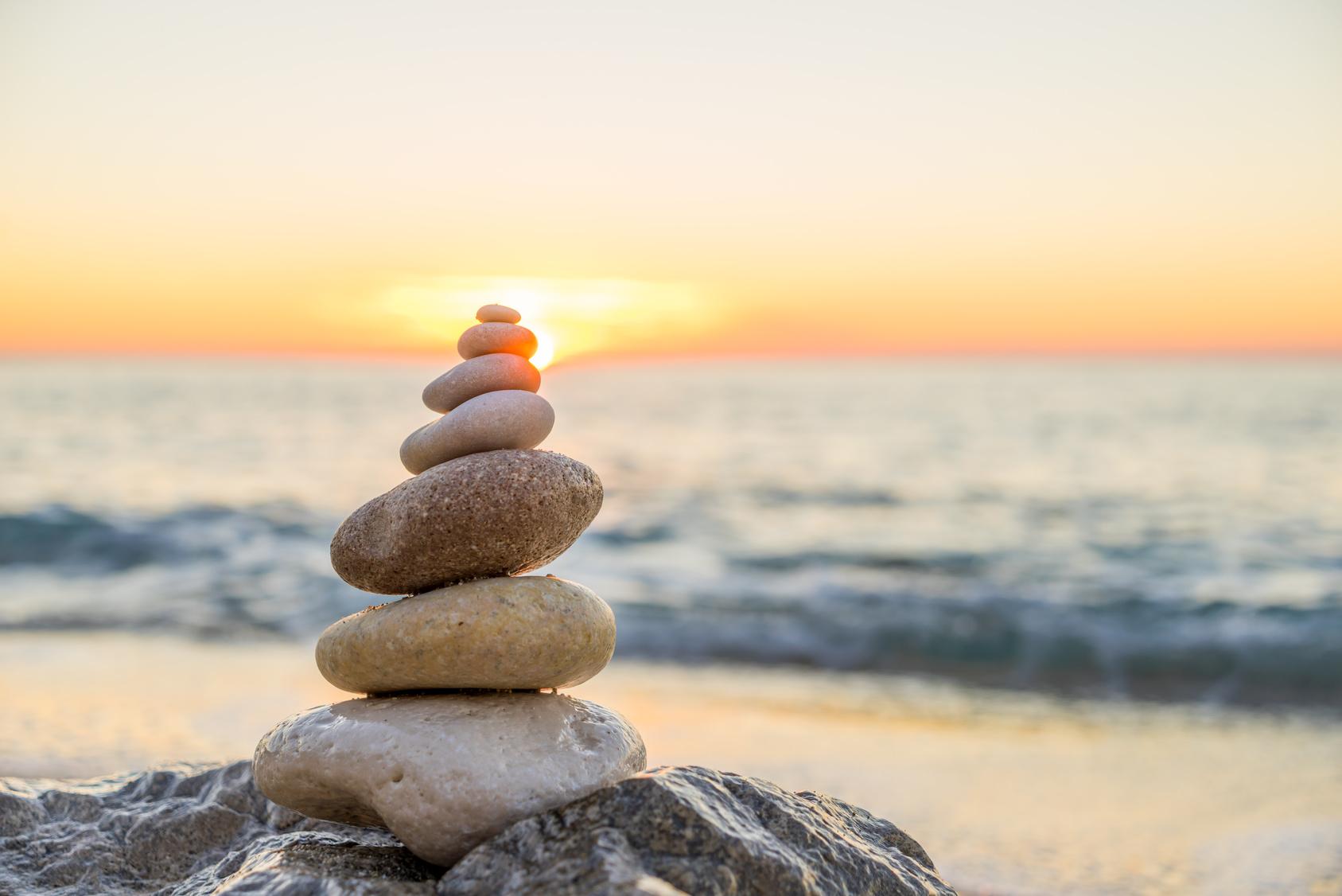 Stones pyramid on sand symbolizing zen, harmony, balance. Ocean